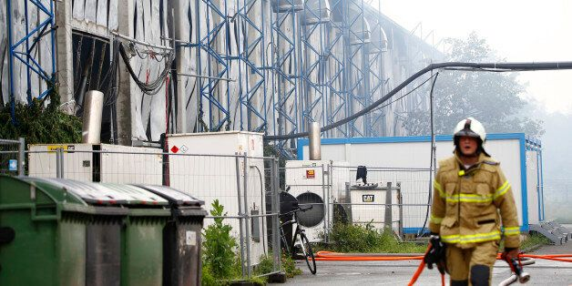 Un pompier marche devant un centre d'expositions utilisé comme foyer de migrants à Dusseldorf, en Allemagne,...