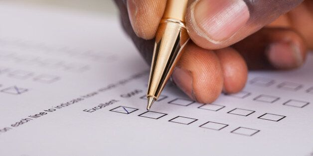 Close-up Of Businessman Filling Customer Survey