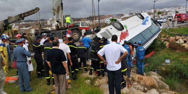 Rescue workers check the debris of an overturned tourist bus in northern Morocco September 8, 2010. Eight...
