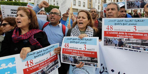 Members of the Moroccan Human Rights Association (AMDH) hold placards and shout slogans during a demonstration...