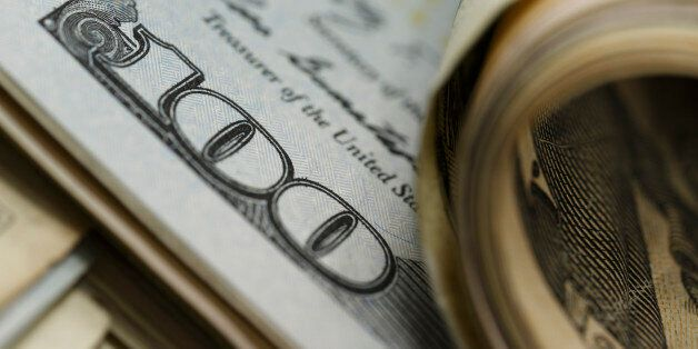 Closeup of curled and flat $100 bills ; shot with very shallow depth of