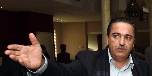 Tunisian businessman, Chafik Jarraya (L), greets Awad Mohammed Abdul-Sadiq (C), the first deputy head...
