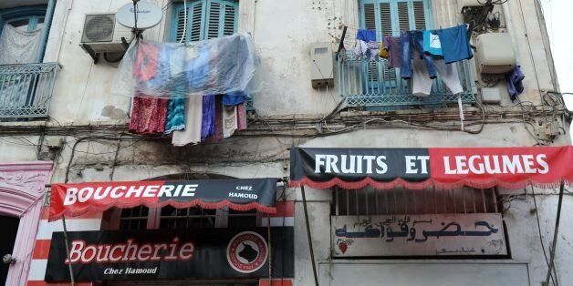 Clothes hang above shops bearing the colours of the Union Sportive Medina d'Alger (USMA) football club...