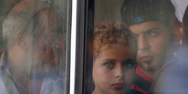 A rescued migrant child looks out of the window of a police bus after arriving at the Armed Forces of...