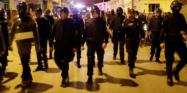 Riot police walk in the street of northern town of Al-Hoceima as thousands of Moroccans shout slogans...
