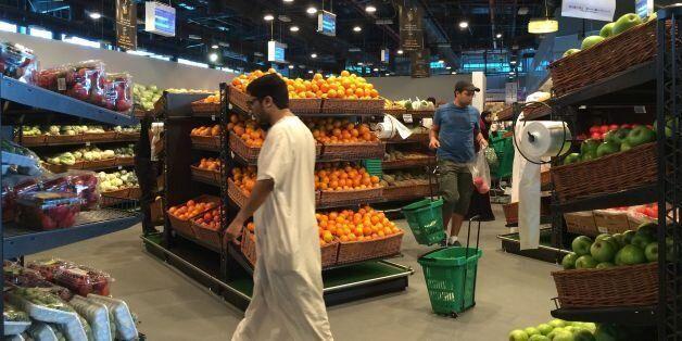 Customers are seen shopping at the al-Meera market in the Qatari capital Doha, on June 10, 2017. Saudi...