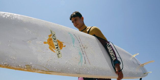 Ali Kassem, a 17-year-old Syrian refugee, carries his surfboard on a beach in the town of Jiyeh, south...