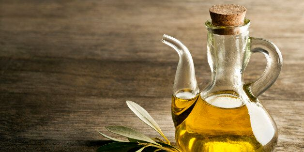Olive oil and olive branch on the wooden
