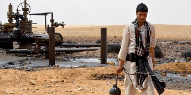 A local walks near a petroleum pumping station in El Kamour, in Tunisia's southern state of Tatatouine,...