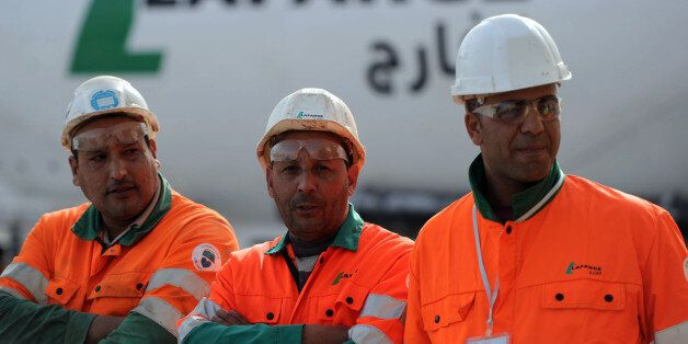 Workers at the Lafarge cement factory, await the arrival of French prime minister and his Algerian counterpart,...
