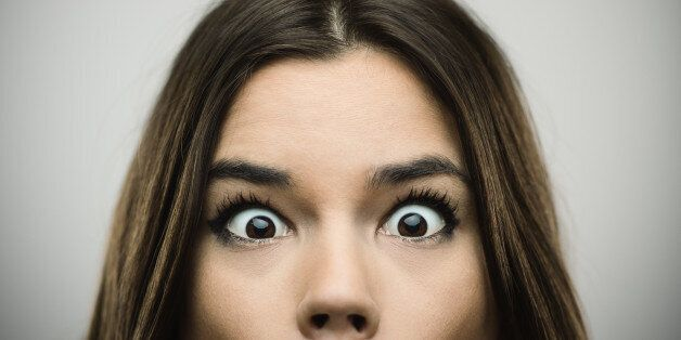 Close-up portrait of happy young woman with surprised face. Cheerful female is against gray background....