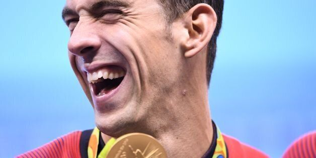 TOPSHOT - USA's Michael Phelps poses with his gold medal during the podium ceremony of the Men's swimming...