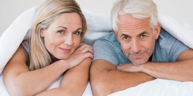 Senior romantic couple under a white duvet in the bed. Happy mature couple lying down in their bed and...