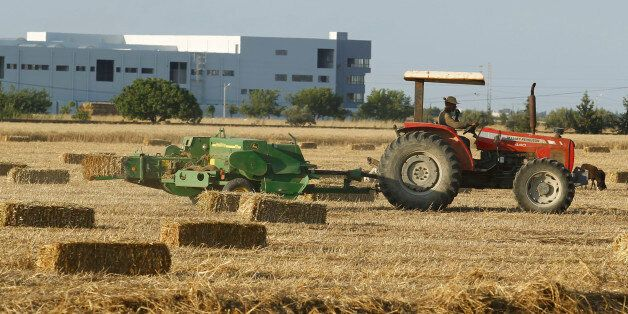 A tractor pulls a hay baler after reaping wheat at a field in Tunis June 18, 2014. REUTERS/Zoubeir Souissi...