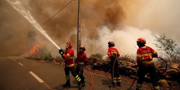Firefighters work to put out a forest fire in the village of Sandinha, near Gois, Portugal, June 20,...