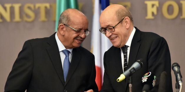 Algerian Foreign Minister Abdelkader Messahel (L) and his French counterpart Jean-Yves Le Drian hold...