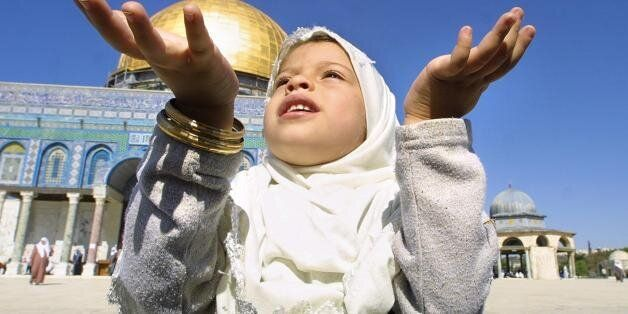 A Muslim Palestinian girl prays in front of the Dome of the Rock in the Al-Aqsa mosque compound in the...