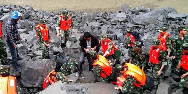 CORRECTION - Chinese military police and rescue workers are seen at the site of a landslide in in Xinmo...