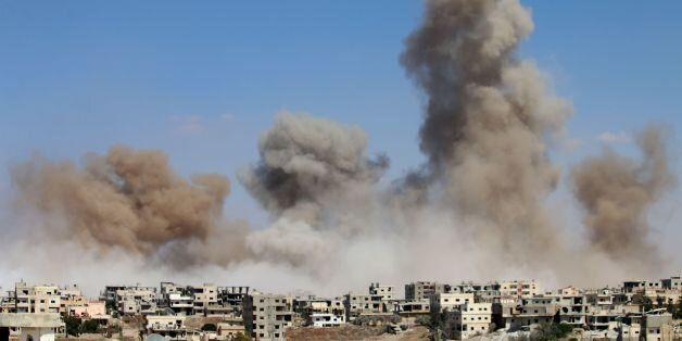 TOPSHOT - Smoke rises following a reported air strike on a rebel-held area in the southern Syrian city...