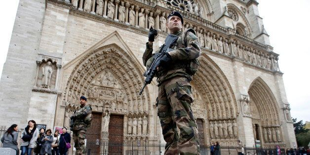French police stand at the scene of a shooting incident near the Notre Dame Cathedral in Paris, France,...