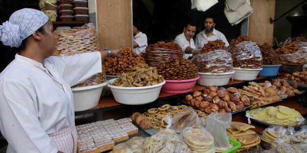 A vendor sells traditional cakes of fried honey and flour pastries to customers ahead of Ramadan in the...