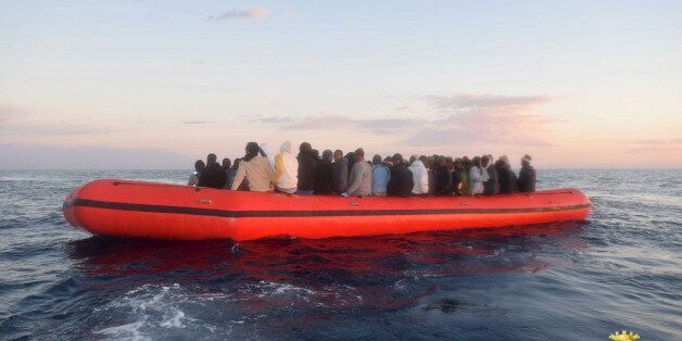 Migrants sit in their boat during a rescue operation of 219 migrants by Italian naval vessel Bettica...