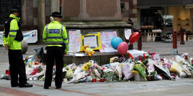 Police officers stand next to floral tributes left for the victims of an attack on concert goers at Manchester...