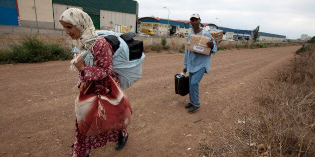 Moroccans carry goods to be taken across the border from Spain's North African enclave of Melilla into...