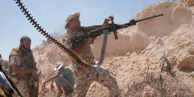A fighter of Libyan forces allied with the U.N.-backed government fires a weapon during a battle with...