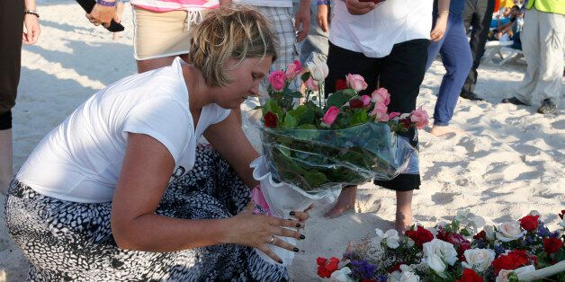 An unidentified tourist places flowers at the scene of Friday's shooting attack in the coastal town of...
