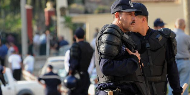 Algerian policemen secure the site of the blast carried by a suicide bomber in front of the gate of the...