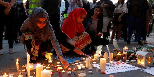 Women light candles following a vigil in central Manchester, Britain May 23, 2017. REUTERS/Peter