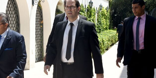 Tunisia's premier-designate Youssef Chahed (C) arrives to give a press conference to present his proposed...