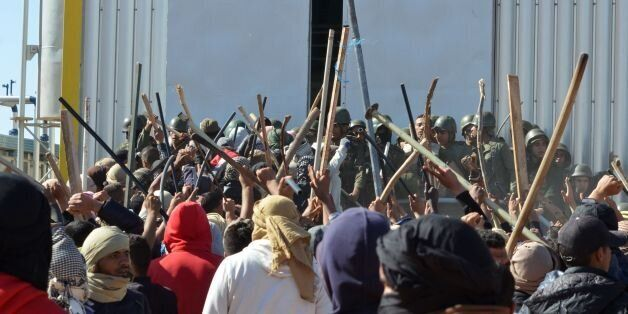 Tunisian protesters comfront security forces outside the El Kamour oil and gas pumping station, in the...