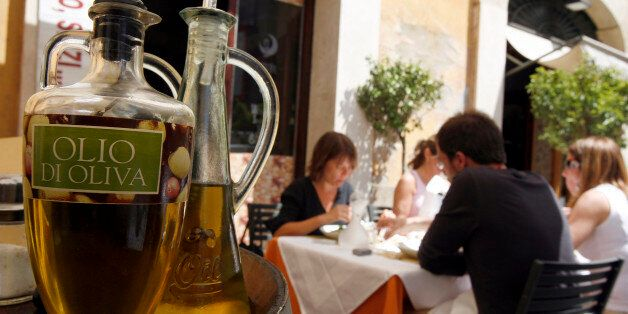 Diners sit near bottles of olive oil at a restaurant in Rome May 17, 2007. When you buy a bottle of olive...