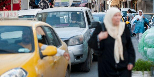 TUNIS, TUNISIA - AUGUST 14: Women go their way next to cars in the Old Quarter in Tunis, Tunisia, on...
