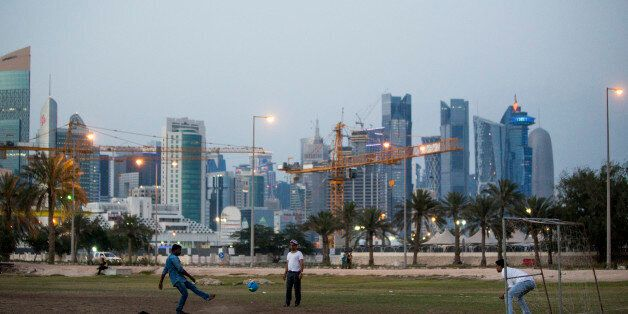 DOHA, QATAR - APRIL 09: Migrant workers play football on an area of wasteland beneath the sky scrapers...