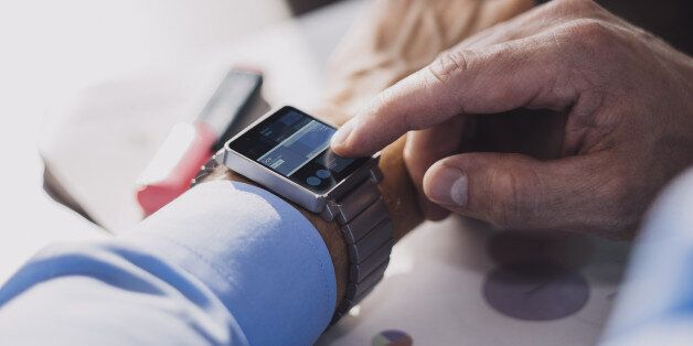 Businessman using smart watch to check stock exchange