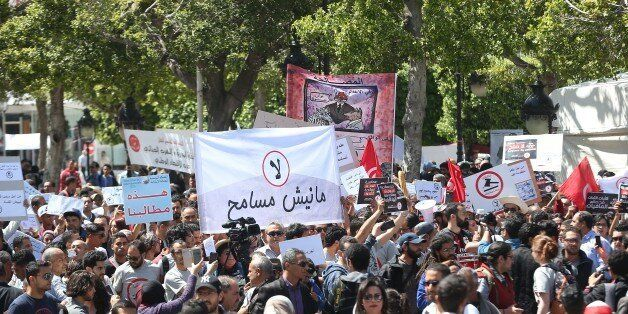 TUNIS, TUNISIA - APRIL 29: People hold banners during a protest against government's bill on Economic...