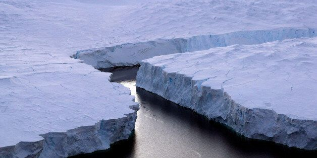 An enormous iceberg (R) breaks off the Knox Coast in the Australian Antarctic Territory on January 11,...