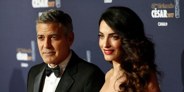 Actor George Clooney and his wife Amal pose as they arrive at the 42nd Cesar Awards ceremony in Paris,...