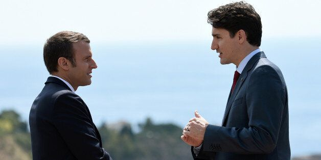 Canadian Prime Minister Justin Trudeau (R) and French President Emmanuel Macron talk as they attend the...