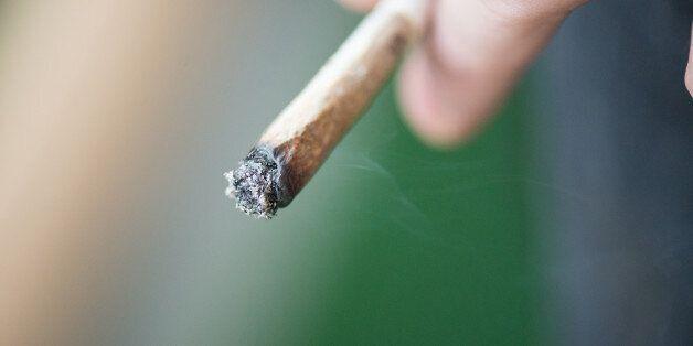 Man smoking marijuana cigarette soft drug in Amsterdam,