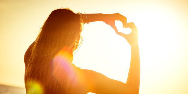 Young woman at the beach, making the shape of a heart with her hands, towards the