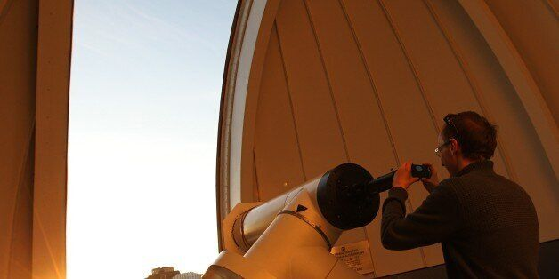 A man takes a picture through a telescope of Venus transiting across the Sun at the Vienna Urania observatory...