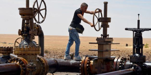 A local turns the wheel of a petroleum pumping station in El Kamour, in Tunisia's southern state of Tatatouine,...