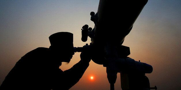 An official looks through a telescope for the sighting of the new moon for the start of the Muslim fasting...