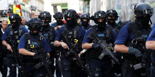 Armed police officers walk near Borough Market after an attack left 7 people dead and dozens injured...