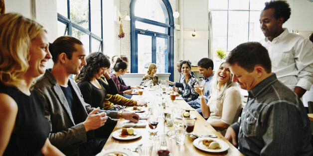 Laughing group of friends sitting at table in restaurant eating