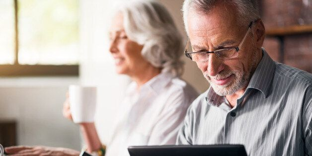 Daily life. Old grey man in glasses using laptop while woman drinking tea and